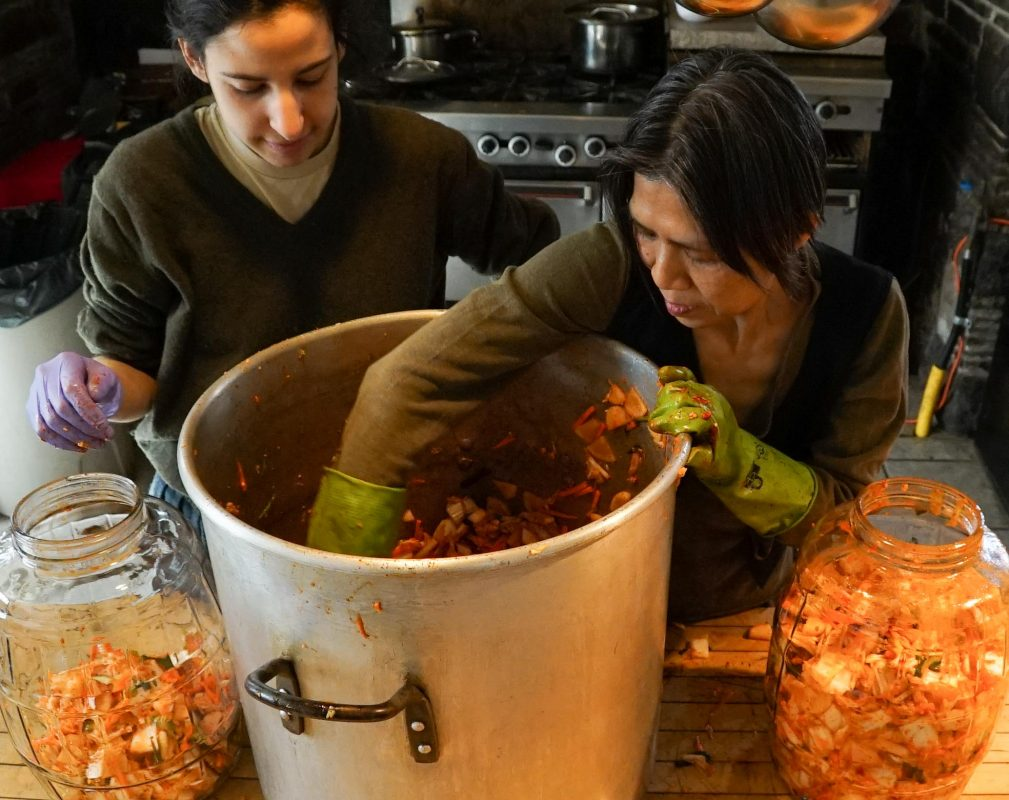 A big batch requires a big pot. Co-cook Laura Cohen looks on as Achong blends everything together by hand.