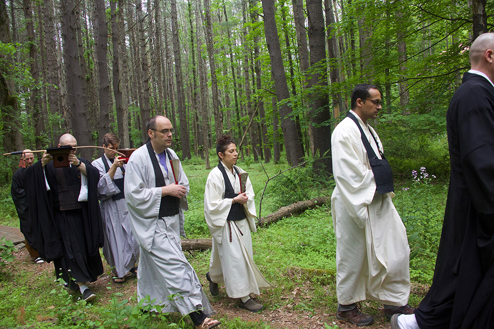 procession walks back through woods