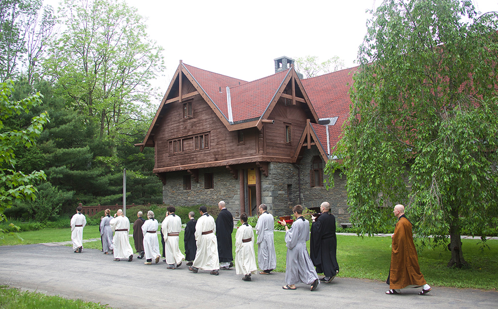 procession walks past front
