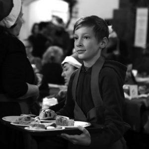 WIN-19-Dana-Dinner---boy-carries-desserts-bw